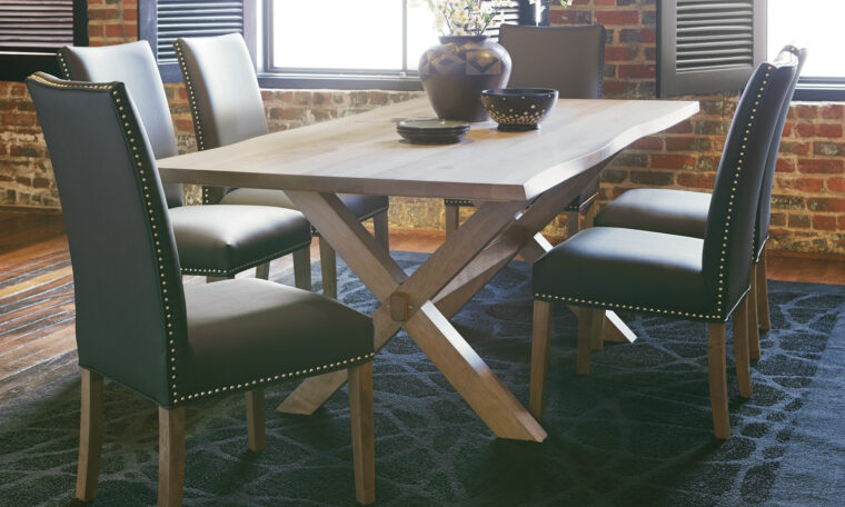 Beautiful customizable dining room table with natural live edge on the table edge and black leather chairs