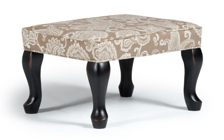 0082 queen anne ottoman is a victorian styled ottoman with a beige and white paisley pattern accented with antique black legs