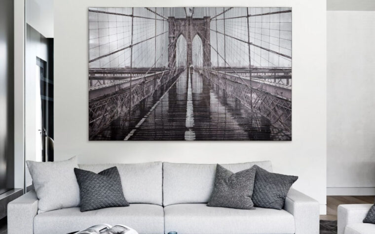 hanging in a modern living room with a wite sofa the iconic art piece is a picture of close up angle of the brooklyn bridge