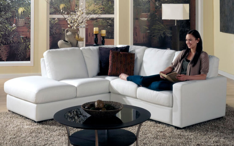 westend sectional is a transitional sectional in white leather with lady sitting on the sectional