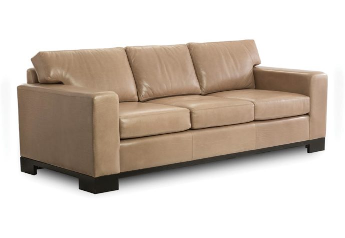 front angle of modern leather sofa from vogel in toronto, on showing a tan leather with espresso wood finish