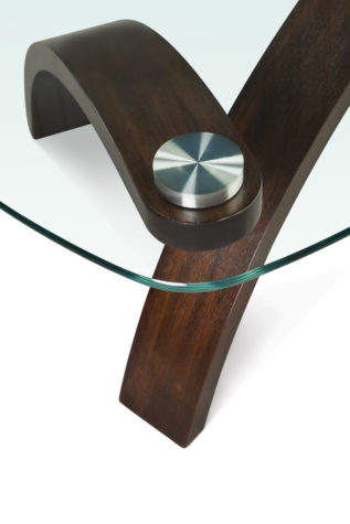 The Allure Pie Shaped Cocktail Table is constructed from walnut veneer, plkwood solids, glass, and stainless steel pucks