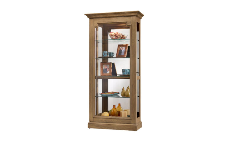 the caden curio cabinet is in a natural finish and has glass sliding doors to showcase your collectables