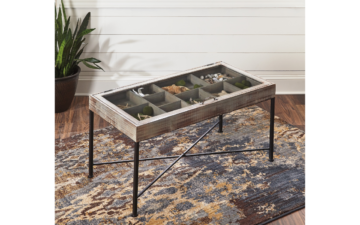 shellmond cocktail table is finished in an anitque grey finish and accented with black legs. It features a top that opens and you can store thigns under the glass top.