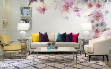 Summery seating area with colourful throw pillows on tan furniture and a floral mural on the background wall