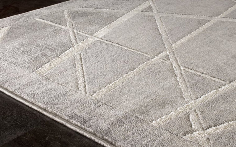 Alaska Area Rug by Kalora - white lines criss-crossing a grey area rug with a grey border (closeup)