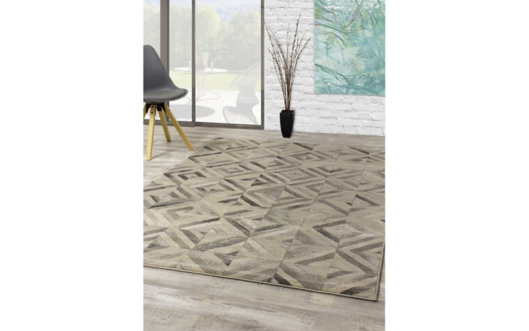 Alaska II Area Rug by Kalora - rug with varying degrees of grey overlapping in a geometric pattern of squares - on the floor of a great room with sliding glass door, and a minimalist mid-century modern chair