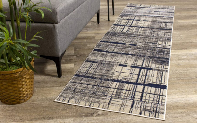 Alaska III Area Rug by Kalora - grey, blue, and cream cross-hatched, antiqued pattern on transitional area rug - rug on wooden floor next to grey leather bench