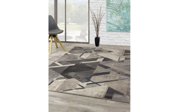 Alida Area Rug by Kalora - geometric abstract area rug in a variety of greys and creams - rug on wooden floor in great room with sliding glass door and minimalist chair