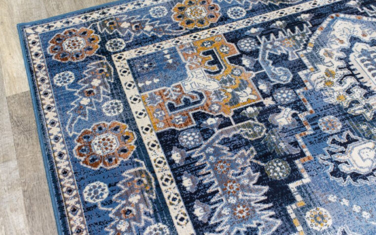 Antika Area Rug by Kalora - deep blue traditional, tapestry-style area rug with intricate orange and cream patterns overlaid (close-up)