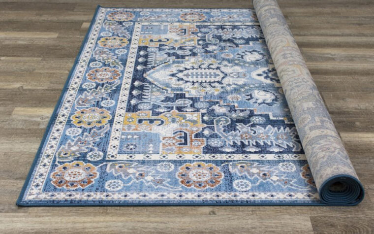 Antika Area Rug by Kalora - deep blue traditional, tapestry-style area rug with intricate orange and cream patterns overlaid (rolled up)