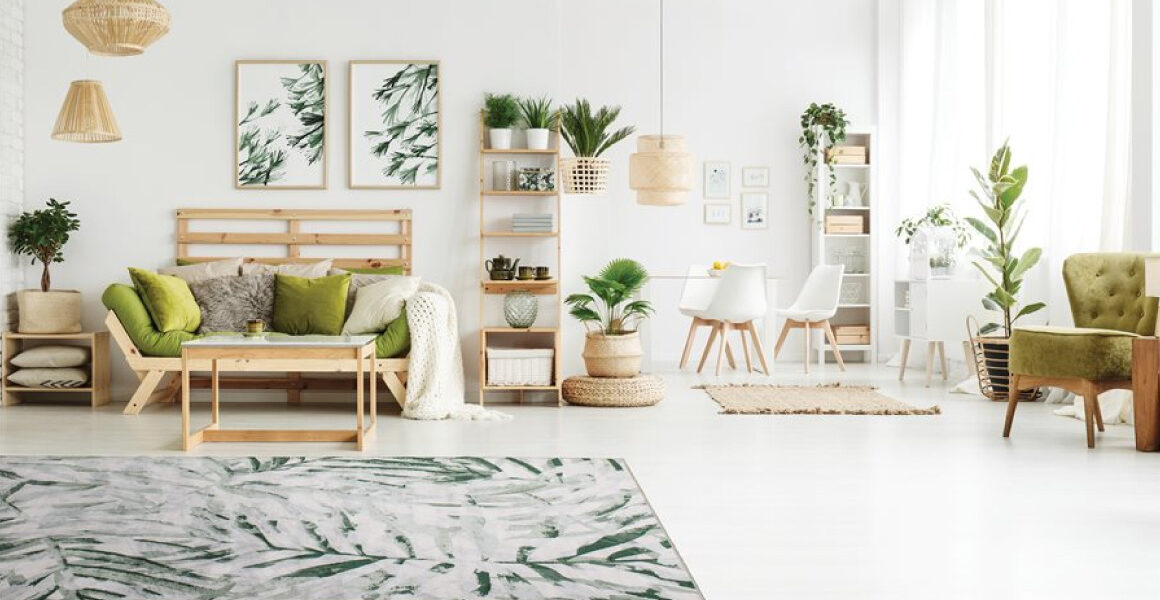 Antika II Area Rug by Kalora - palm branch pattern overlaid on cream background - rug on white floor with Scandinavian wooden furniture and decor