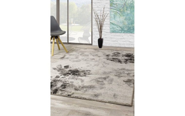 Breeze Area Rug by Kalora - grey and cream floral, antiqued pattern on floor rug; lifestyle photo in modern great room with sliding patio door and minimalist chair