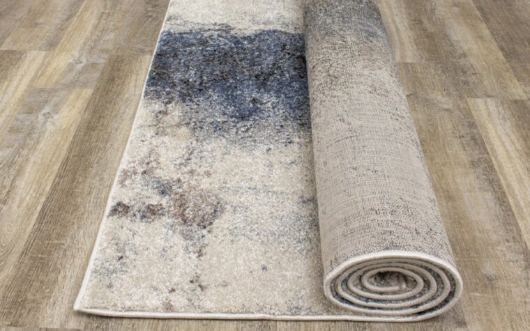 Breeze II Area Rug by Kalora - floor rug with marbled design of cream, black, brown, and teal blue (rolled up)
