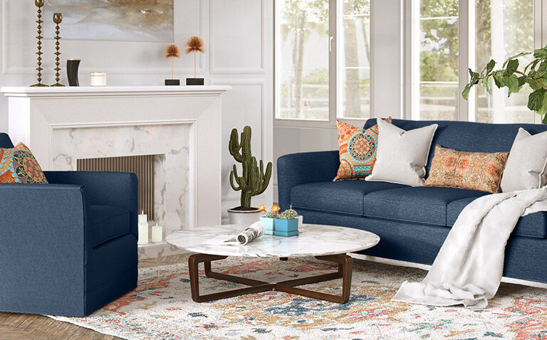 Clarissa collection by Vogel next to a fireplace - upholstered in navy fabric and accented with white and orange throw pillows and a colourful area rug