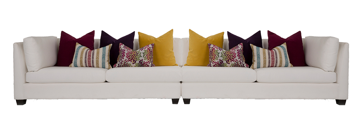 2875 Sectional by Decor-Rest upholstered in an off-white fabric with dark legs and lots of toss cushions in a variety of summery colours (mustard, burgundy, green)