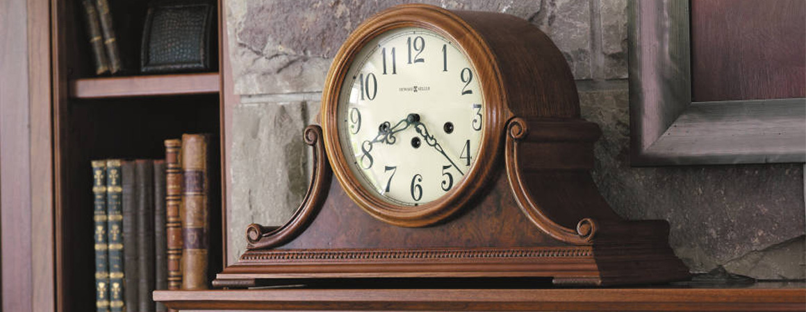 Howard Miller Mantle Clock - medium brown finish - sitting on mantle next to bookshelf