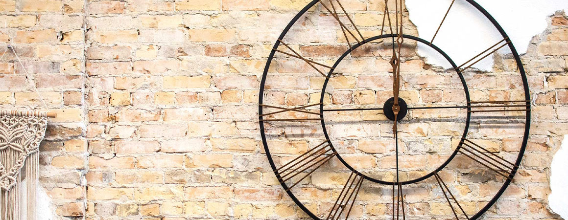 Howard Miller metal Wall Clock on light brick wall