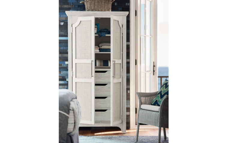 833160 Narrow Coastal Utility Cabinet - sandbar finish on armoire with two doors decorated with raffia inserts; situated next to coastal wicker arm chair next to bi-fold patio doors in modern beach house; adjustable shelves and 4 drawers inside