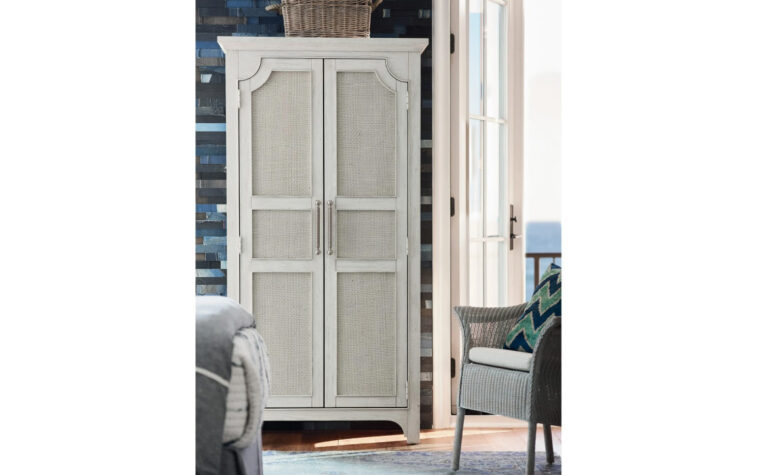 833160 Narrow Coastal Utility Cabinet - sandbar finish on armoire with two doors decorated with raffia inserts; situated next to coastal wicker arm chair next to bi-fold patio doors in modern beach house