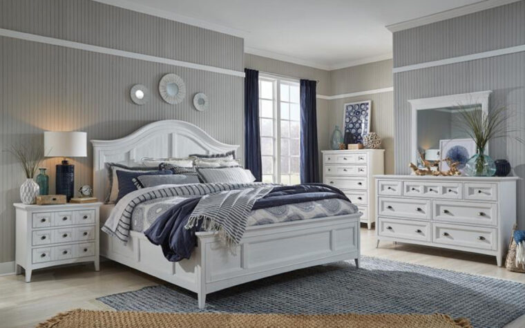B4400 Heron Cove Bedroom Collection - Universal Furniture - relaxed casual bedroom furniture finished in Chalk White; arched headboard pairs with paneled footboard and 2 drawer chests and a nightstand in a bedroom featuring grey wallpaper, an off-grey wooden floor, and a grey area rug, white navy curtains and bedding
