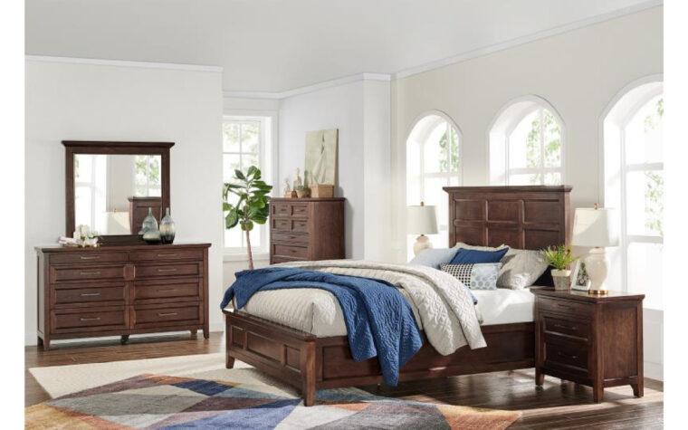 B4993 Hamlin Park Bedroom Collection - Universal Furniture - warm Russet finish and Antique Bronze hardware; fresh and inviting bedroom with blue and white throw blankets across the bed, an area rug on the floor, and arched windows letting in lots of natural light