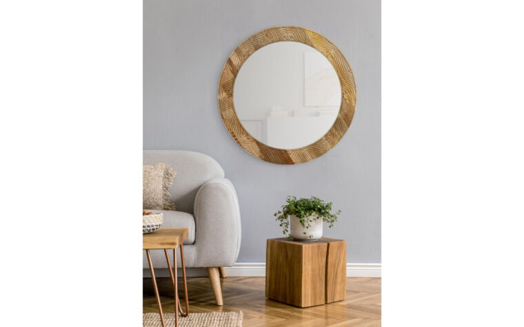 Frederick Mirror - Renwil - carved mango wood frame with natural finish surrounding round mirror; hanging on grey wall in mid-century modern living room with grey sofa and wooden accent tables (chevron style floor)
