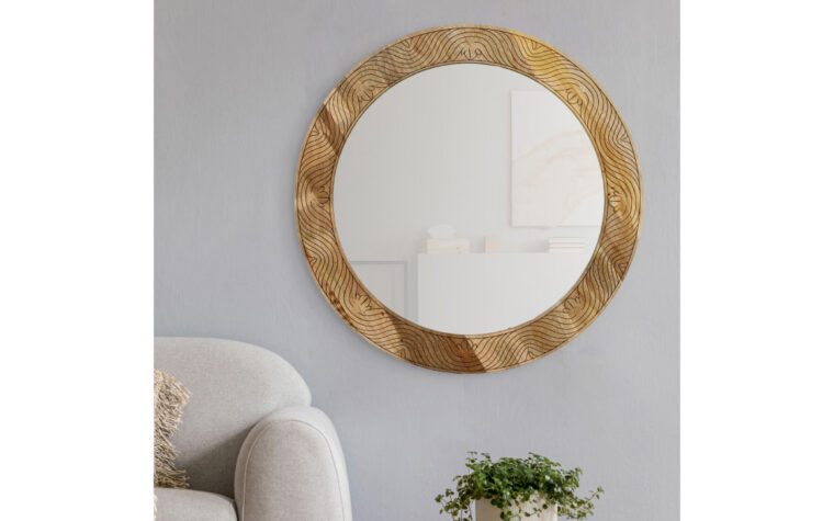 Frederick Mirror - Renwil - carved mango wood frame with natural finish surrounding round mirror; hanging on grey wall in mid-century modern living room with grey sofa