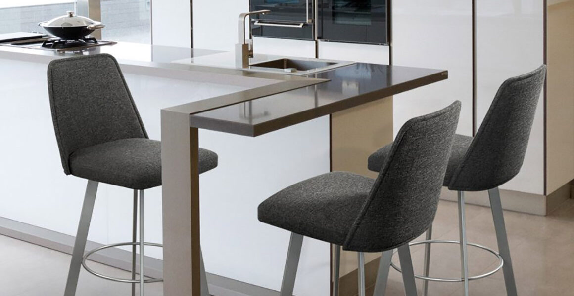 Trica Sofia barstools with full backs upholstered in grey fabric and stationed around a glass-top peninsula in a white, high gloss, condo kitchen