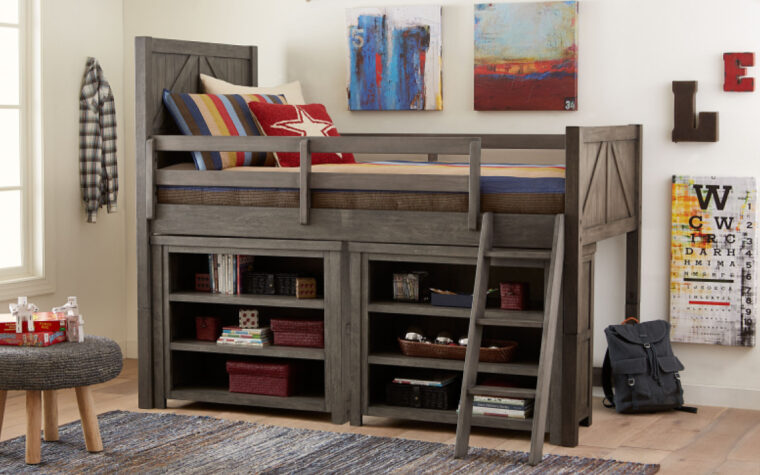 2 Bunkhouse Bookcases positioned under the Loft Bed; staged on a wooden floor next to an area rug and made up with red, blue and yellow bedding in a fun, kid-ish style