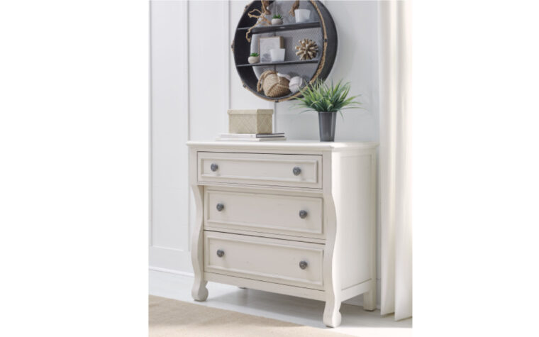 8972-2100 - Lake House Accent Chest - white - 3 drawers with 2 knobs each - wavy design - nickel hardware; staged against vertical shiplap wall with mirrored, circular display cabinet above and wooden floor beneath