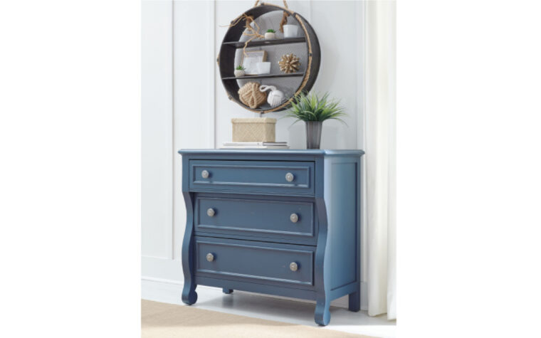 8972-2100 - Lake House Accent Chest - blue - 3 drawers with 2 knobs each - wavy design - nickel hardware; staged against vertical shiplap wall with mirrored, circular display cabinet above and wooden floor beneath