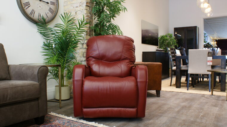 Palliser recliner upholstered in red leather; perfect for petite individuals; displayed against greenery in Chervin Furniture & Design showroom