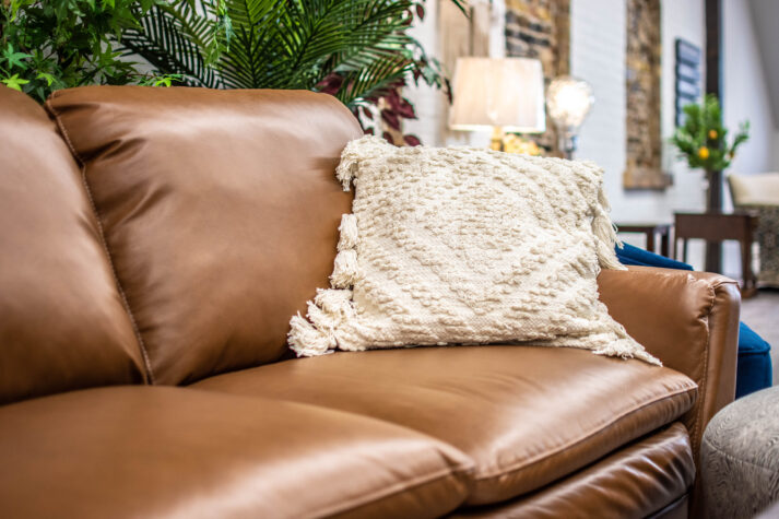Brown leather sofa (close-up) with white throw pillow (Renwil) in Elmira showroom of Chervin Furniture & Design