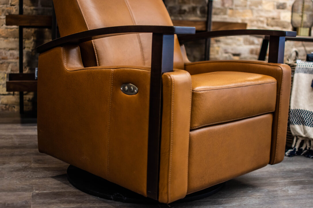Dutailier glider with show-wood arms upholstered in dark caramel-coloured leather with black wood finish