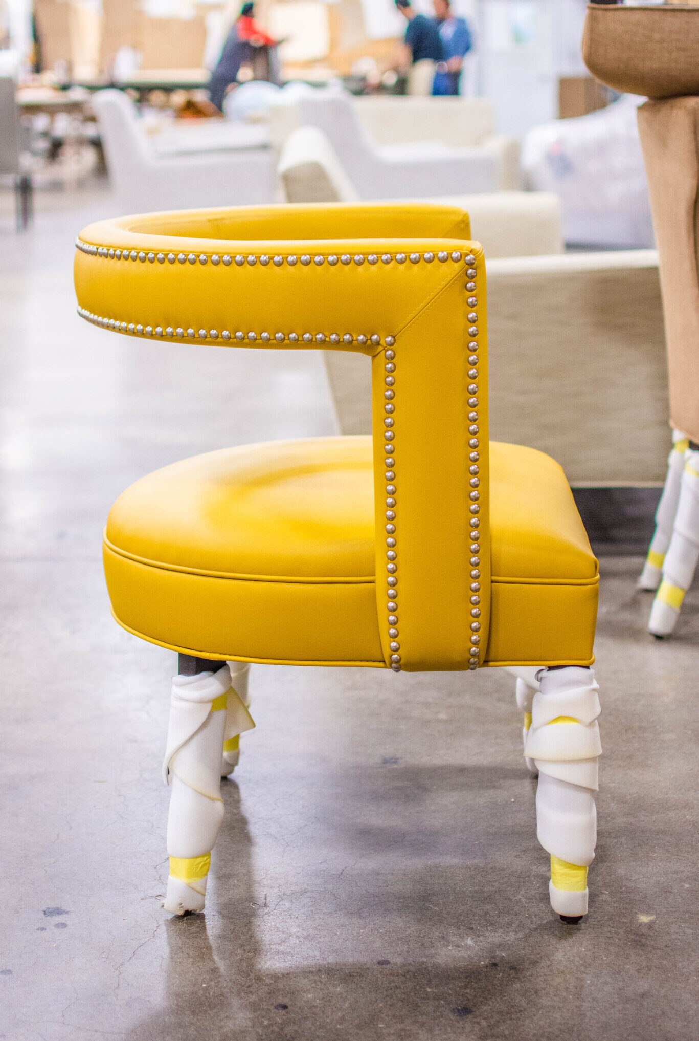 Vogel accent chair in production - featuring nail head trim on vibrant yellow leather