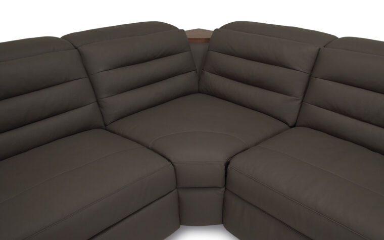 Corner seat of dark grey leather sectional with tufted back cushions